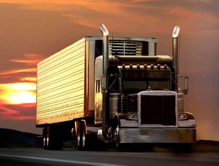 Semi driving down the road with a sunset in the background.