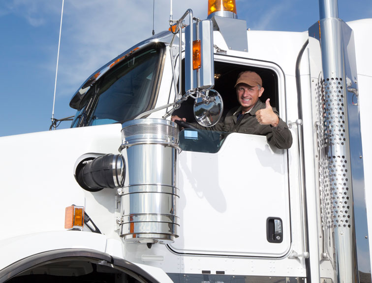 Truck driver sitting in driver seat giving a thumbs up out the window.
