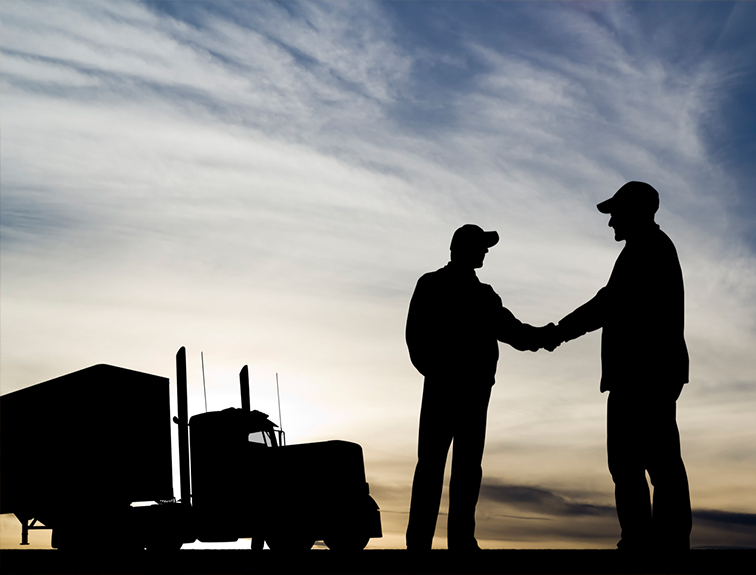 Silhouettes of two men shaking hands with a truck in the background.