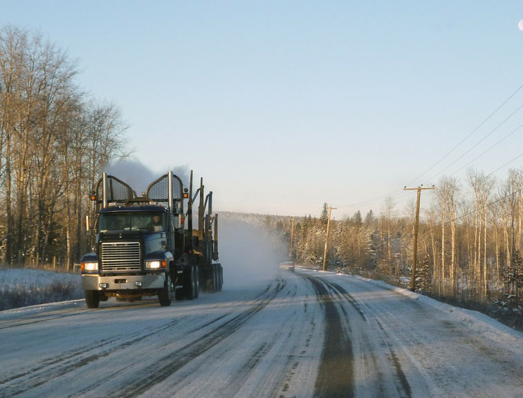Large truck driving down road in winter