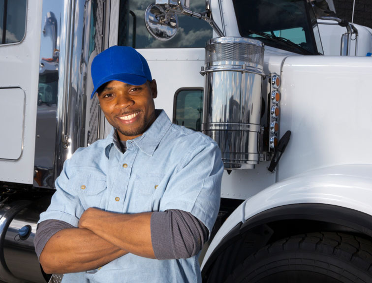 Man standing in front of a truck with arms crossed.