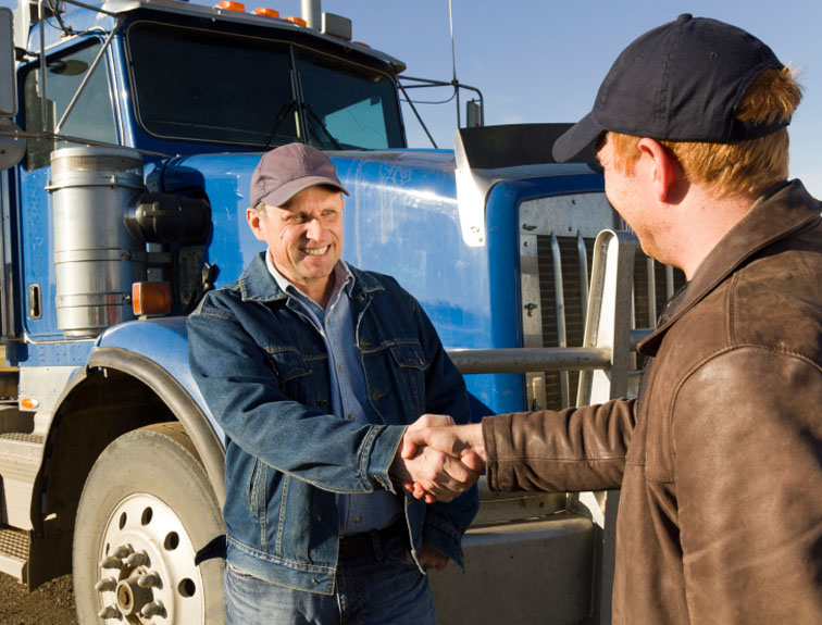 Two men shaking hands with semi in the background.