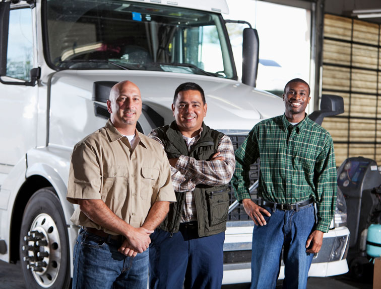 Three truck drivers standing in a row with a semi in the background