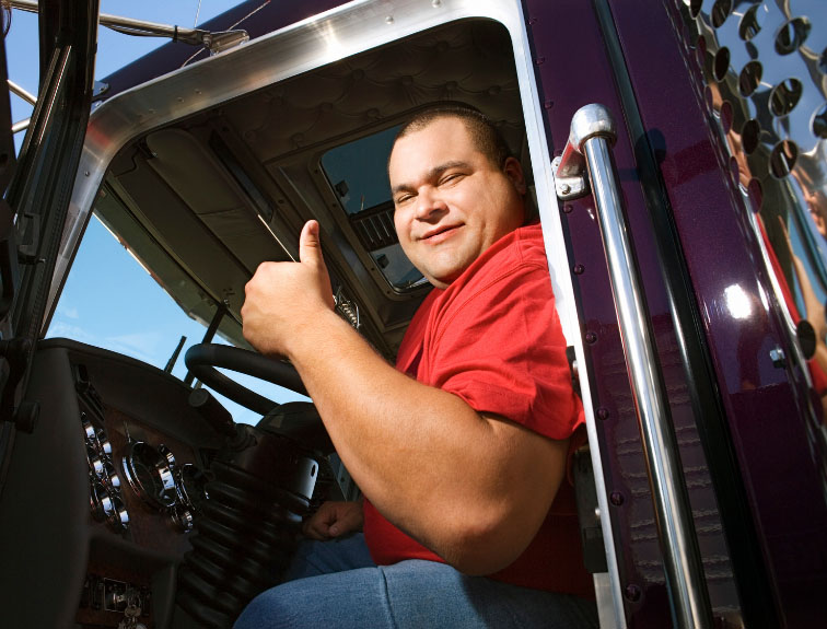 Trucker in the driver seat giving a thumbs up