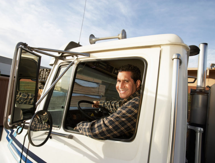 Truck driver sitting in driver seat of a white semi