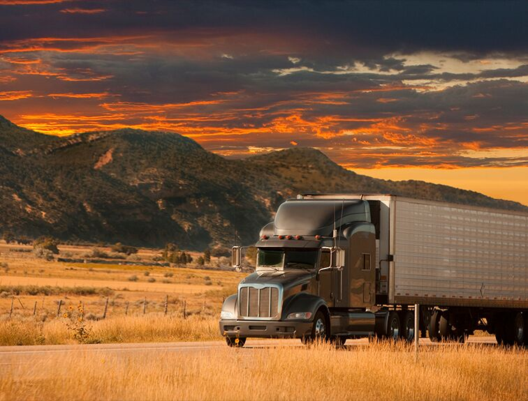 Semi truck driving on road with sunset behind